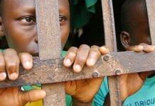 Two young prisoners stand behind bars in a jail in Abomey, Benin.
