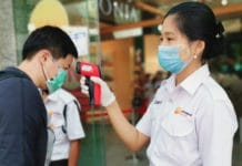 Staff check customers' temperatures at a shopping mall entrance in Yangon, Myanmar.