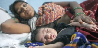 A two day old child sleeps next to its mother at a maternity ward in Rajasthan, India.