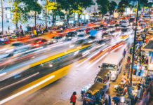 A time-lapsed scene of a busy street at night in Bangkok, Thailand.
