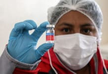 A nurse in Boliva holds up a dose of flu vaccination.
