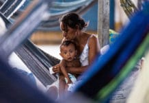 A mother takes care of her baby inside a gymnasium that has been turned into a refugee settlement in Pintolandia, Brazil.