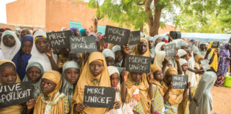 Young girls in the village of Danja in Niger hold signs in support of the Spotlight Initiative