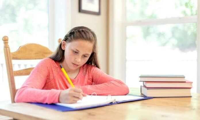 Girl writing letter at table