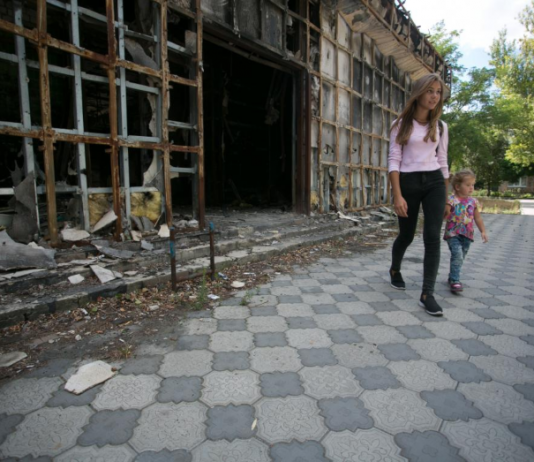 Woman and child walking next to bombed building