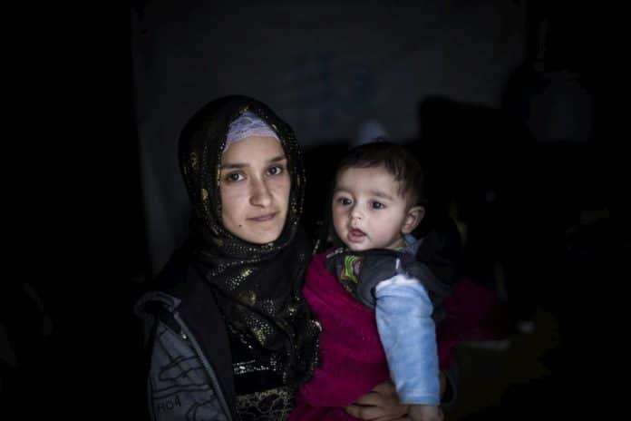 Hakima, 21, holds her four-month-old baby, Jad, at Bar Elias refugee settlement in Lebanon