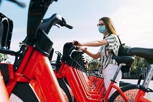 Woman wearing protective face mask taking a rented electric bicycle. Taking an electric bike. Electric bicycle rental.