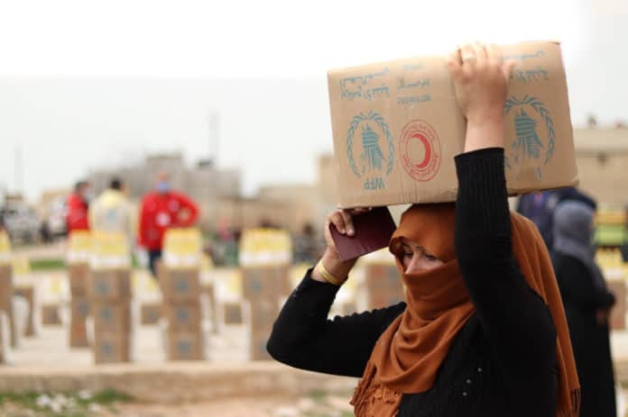 A-woman-collects-food-in-Deir-Hafer-60-km-from-Aleppo-Syria-Photo-WFP-Khudr-Alissa