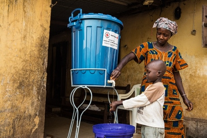 Mother washing the child's hands in Guinea with chlorine-treated water to prevent getting infected with Ebola. UN Photo:Martine Perret